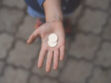 selective focus photography of person's palm with two coins