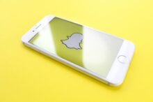 silver iPhone 6 on top of yellow wooden surface