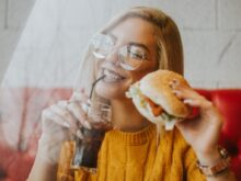woman sitting while holding burger