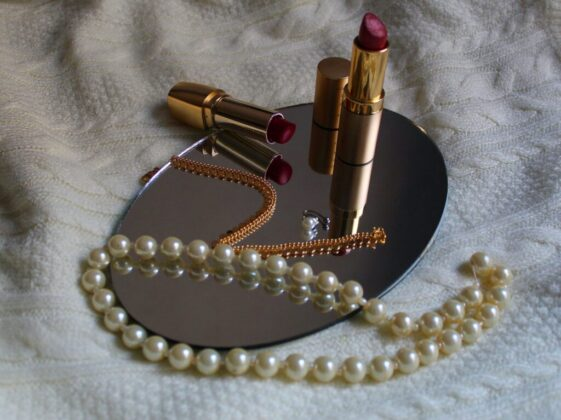 white pearl necklace beside pink lipstick