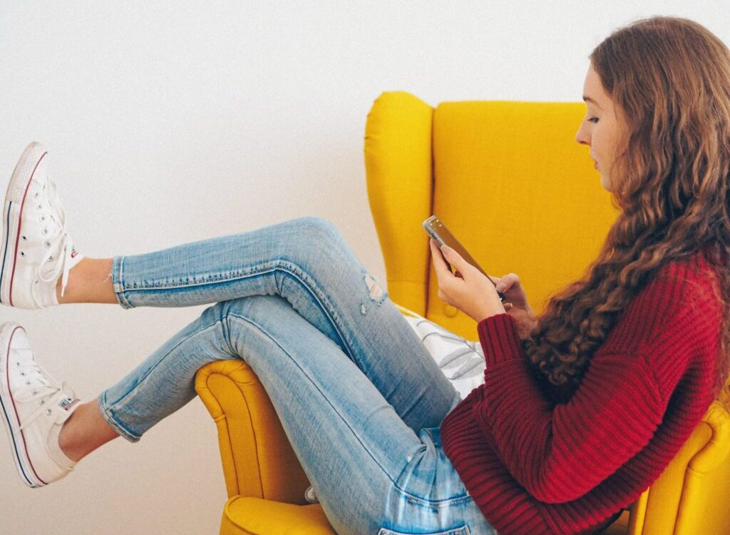 woman in red sweater and blue denim jeans sitting on yellow couch