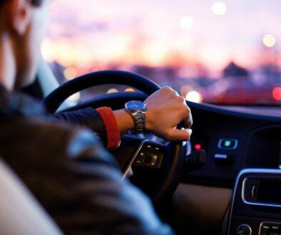 man driving a car wearing wrist watch