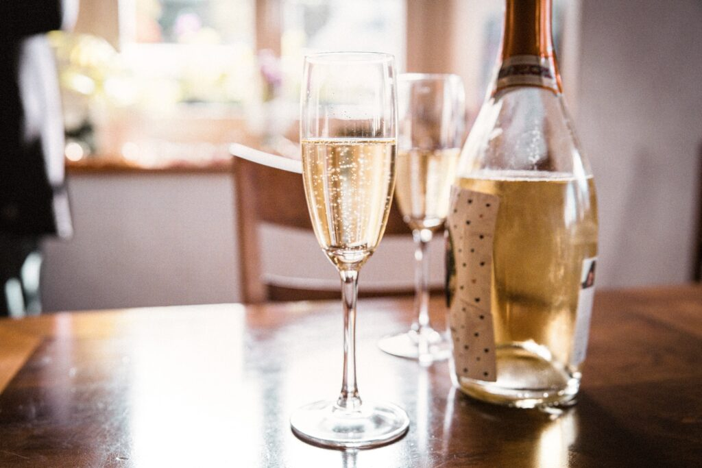 clear wine glass beside clear glass bottle on brown wooden table